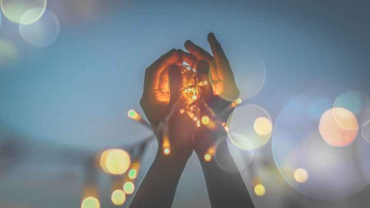 person s hand with light bokeh